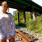 Fourth pic of Amateur solo girl poss non nude on train tracks in tight dress and glasses